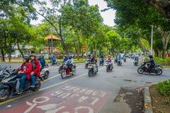 BALI, INDONESIË - MAART 08, 2017: Niet geïdentificeerde mensen die motorfietsen en auto's in het weghoogtepunt drijven van verkee Stock Foto