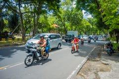 BALI, INDONESIË - MAART 08, 2017: Niet geïdentificeerde mensen die motorfietsen en auto's in het weghoogtepunt drijven van verkee Stock Afbeelding