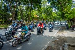 BALI, INDONESIË - MAART 08, 2017: Niet geïdentificeerde mensen die motorfietsen en auto's in het weghoogtepunt drijven van verkee Royalty-vrije Stock Fotografie