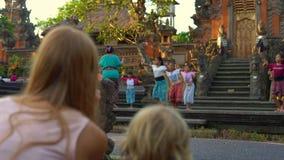 BALI, INDONESIË - MAG Slowmotion schot 16 van een jonge vrouw en haar weinig zoon in de Saraswati-Tempel in Ubud-dorp stock videobeelden