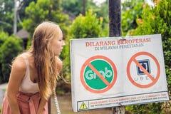 BALI, INDONESIË - 21 Mei, 2018: De jonge vrouw bekijkt protestteken op een muur in Indonesiër die tegen Uber en Greep bezwaar heb royalty-vrije stock afbeelding