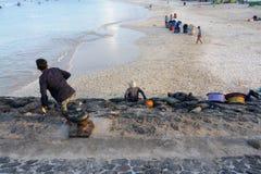 BALI/INDONESIA- 15-ОЕ МАЯ 2019: Некоторые рыболовы нося рыб отдыхают на краю гавани Они ждали рыбную ловлю стоковые изображения