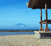 Bali, Indonesia. View of a dormant volcano from a Bali beach house. In the distance, a woman scours the shallows for clams stock photos