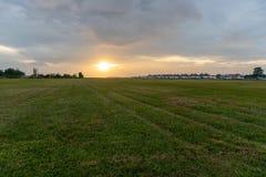 BALI/INDONESIA-APRIL 5 2019年:从跑道领域的拉伊巴克罕Aiport景色,当日落和多云天空 库存照片