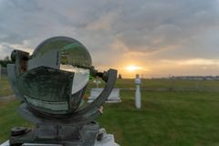 BALI/INDONESIA-APRIL 05 2019: Campbell-stoke at Ngurah Rai Meteorology Station with green grass and orange sunset under the cloudy stock photography