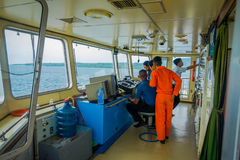 BALI, INDONESIA - APRIL 05, 2017: Ferry boat pilot command cabin with the captain operating the machines with a many Stock Images