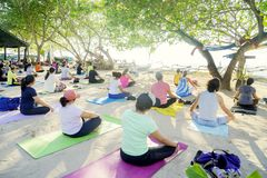 Crowded visitors practicing yoga on the Sanur beach. BALI - Indonesia. April 12, 2018: Image of crowded visitors practicing yoga on the Sanur beach at morning stock photo