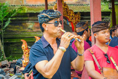 BALI, INDONESIA - APRIL 05, 2017:Unidentified man playing some musical instrument, flute and wearing dark sunglases. Inside of the Ubud tmple in Bali located in Royalty Free Stock Image