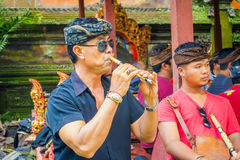 BALI, INDONESIA - APRIL 05, 2017: Unidentified man playing some musical instrument, flute and wearing dark sunglases. Inside of the Ubud tmple in Bali located Royalty Free Stock Photos