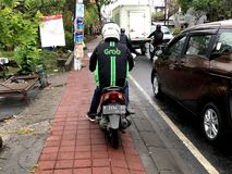 Grab motor taxi driver. Bali, Indonesia - August 17, 2018: Backside of a unidentifiable Grab motor taxi driver standing boy the side of the road. Grab is a motor stock photography