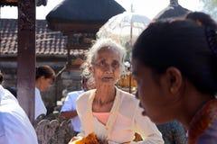 BALI INDONESIA-AUGUST 29,2012: En äldre kvinna kom till en religio Arkivbilder