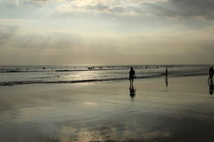 Bali; Indonesia; BaliIndonesia; surf; Surfing; beach, beachfront; ocean; Indianocean; sunset. Silhouettes of people walking at sunset on the ocean; rays of light Stock Photos
