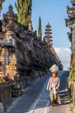 Bali, Indonesia - circa October 2015: Old lady carry offerings at Pura Ulun Danu Batur, Bali,  Indonesia Royalty Free Stock Photography