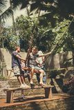 BALI, INDONESIA - 5 DE DICIEMBRE DE 2017: El grupo de hombres que ayudan a un turista se sienta en oscilaciones en el acantilado  Fotos de archivo