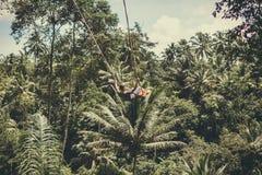 BALI, INDONESIA - 5 DE DICIEMBRE DE 2017: Hombre turístico joven que balancea en el acantilado en la selva tropical de la selva d Imágenes de archivo libres de regalías