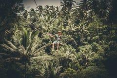 BALI, INDONESIA - 5 DE DICIEMBRE DE 2017: Hombre turístico joven que balancea en el acantilado en la selva tropical de la selva d Fotos de archivo libres de regalías