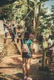 BALI, INDONESIA - 5 DE DICIEMBRE DE 2017: La mujer que mira en el grupo de hombres que ayudan a un turista se sienta en oscilacio Imagen de archivo libre de regalías