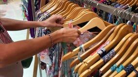 Bali, Indonesia - 20 de diciembre de 2017: Mujer que elige la ropa en la tienda de la moda Mujer del comprador en el boutique almacen de metraje de vídeo