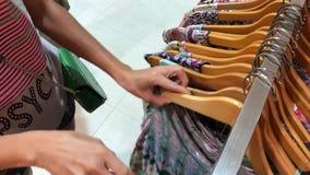 Bali, Indonesia - 20 de diciembre de 2017: Mujer que elige la ropa en la tienda de la moda Mujer del comprador en el boutique metrajes