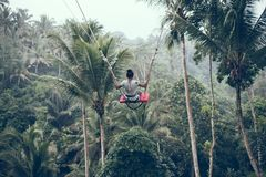 BALI, INDONESIA - 26 DE DICIEMBRE DE 2017: Mujer que se divierte un oscilación en la selva Mujer que balancea en la selva tropica Foto de archivo