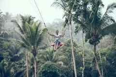 BALI, INDONESIA - 26 DE DICIEMBRE DE 2017: Mujer que se divierte un oscilación en la selva Mujer que balancea en la selva tropica Fotos de archivo libres de regalías