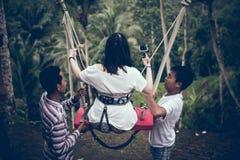 BALI, INDONESIA - 26 DE DICIEMBRE DE 2017: Mujer que se divierte un oscilación en la selva Mujer que balancea en la selva tropica Fotografía de archivo libre de regalías