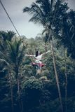 BALI, INDONESIA - 26 DE DICIEMBRE DE 2017: Mujer que se divierte un oscilación en la selva Mujer que balancea en la selva tropica Foto de archivo libre de regalías