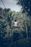 BALI, INDONESIA - 26 DE DICIEMBRE DE 2017: Mujer que se divierte un oscilación en la selva Mujer que balancea en la selva tropica Imagen de archivo
