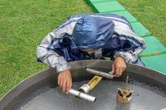 BALI/INDONESIA- 21 DE DICIEMBRE DE 2017: Un observador meteorológico comprueba el termómetro del agua para asegurarse de la tar foto de archivo libre de regalías