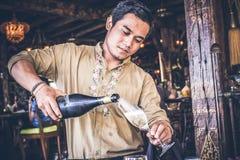 BALI, INDONESIA - 3 DE JULIO DE 2017: Champán de colada del hombre asiático en vidrio Isla tropical Bali, Indonesia imágenes de archivo libres de regalías