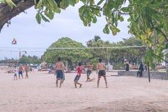 BALI, INDONESIA - 27 DE JULIO DE 2017: Grupo de amigos que juegan el voleo de la playa - grupo de personas de los Multi-éticas qu Foto de archivo