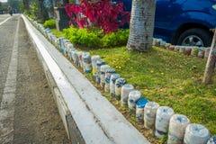 BALI, INDONESIA - 8 DE MARZO DE 2017: Botellas de agua plásticas en el parque en al revés en la fila, reciclada para adornar parq Fotos de archivo