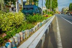 BALI, INDONESIA - 8 DE MARZO DE 2017: Botellas de agua plásticas en el parque en al revés en la fila, reciclada para adornar parq Foto de archivo