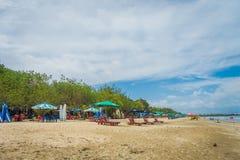 BALI INDONESIA 8 DE MARZO DE 2017: Turistas con marea baja de la última hora de la tarde que dan un paseo en la playa de Legian Fotos de archivo libres de regalías