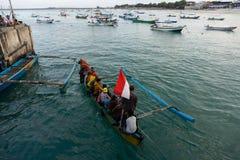 BALI/INDONESIA- 15 DE MAYO DE 2019: algunas personas están en un barco Indonesio-señalado por medio de una bandera tradicional Es fotografía de archivo