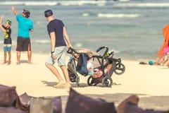 BALI, INDONESIA - 13 DE OCTUBRE DE 2017: Hombre con el carro de bebé en la playa de la isla de Bali, Indonesia Fotografía de la c Imagenes de archivo