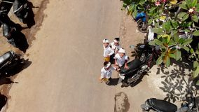 BALI, INDONESIA - 9 DE OCTUBRE DE 2018: vídeo que vuela aéreo 4K de los niños del Balinese en trajes tradicionales imagen de archivo
