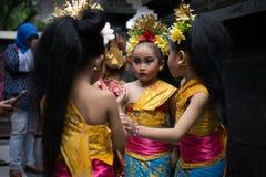 28 bali/indonesia-DECEMBER 2017: Drie jonge Balinese dansers die traditionele Balinese kleren dragen en maken omhoog, voorbereidi stock afbeelding