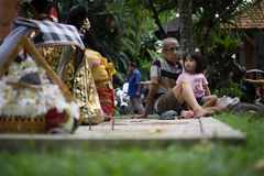 BALI/INDONESIA-DECEMBER 28 2017: dziad dbał dla jego wnuczki towarzyszyć jego wnuczki ogląda sztukę zdjęcie royalty free