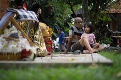 BALI/INDONESIA-DECEMBER 28 2017: en farfar att bry sig för hans sondotter, genom att medfölja hans sondotter som håller ögonen på royaltyfri foto