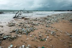 Bali, Indonesia - December 19, 2017: Garbage on beach, environmental pollution in Bali Indonesia. Storm is coming on background. And drops of water are on royalty free stock photos