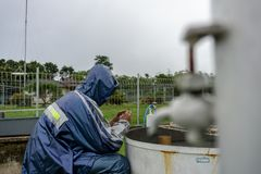BALI/INDONESIA-DECEMBER 21 2017: A meteorological observer checks the water thermometer to make sure the evaporation rate on that stock images