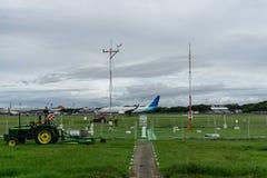 BALI/INDONESIA-DECEMBER 21 2019: några flygplatsrengöringsmedel klippte gräs runt om landningsbanan genom att använda en grä fotografering för bildbyråer