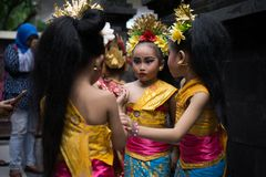 BALI/INDONESIA-DECEMBER 28 2017:Three young Balinese dancers wearing traditional Balinese clothes and make up, were preparing to stock image
