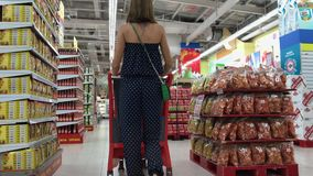 BALI, INDONESIA - DECEMBER 19, 2017: Woman shopping at the supermarket, follow shot from back of young woman with stock video footage