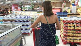 BALI, INDONESIA - DECEMBER 19, 2017: Woman shopping at the supermarket, follow shot from back of young woman with. Trolley stock video