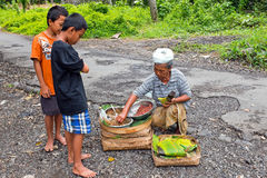 BALI, INDONESIA - DECEMBER 25, 2016: Young boy just got his food Stock Photos