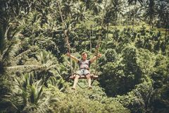 BALI, INDONESIA - DECEMBER 5, 2017: Young tourist man swinging on the cliff in the jungle rainforest of a tropical Bali Stock Photo