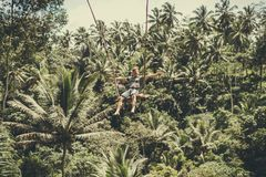 BALI, INDONESIA - DECEMBER 5, 2017: Young tourist man swinging on the cliff in the jungle rainforest of a tropical Bali Royalty Free Stock Photography