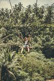 BALI, INDONESIA - DECEMBER 5, 2017: Young tourist man swinging on the cliff in the jungle rainforest of a tropical Bali Stock Photos